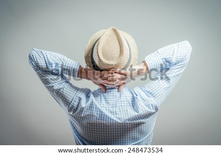 Young relaxed man with hands behind head - stock photo