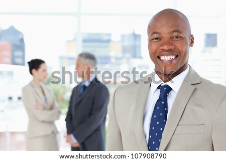 Young relaxed manager standing upright while showing a great smile - stock photo