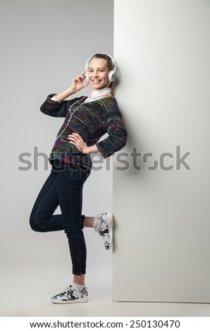 Young relaxed woman leaning on wall listening to music with headphones.Full length portrait. - stock photo