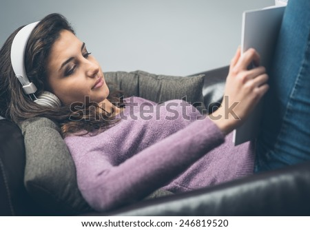 Young  relaxed woman on sofa with headphones reading a book - stock photo