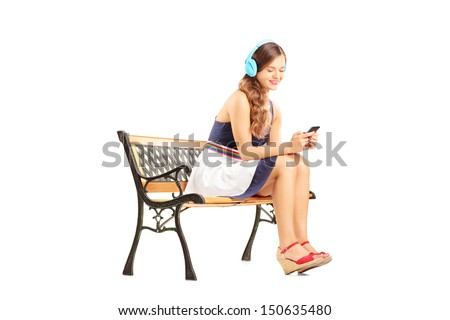 Young relaxing female sitting on a wooden bench and listening music isolated on white background - stock photo