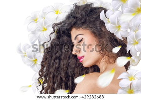 Young relaxing woman portrait with plumeria flowers - stock photo