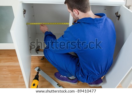 Young repair man measuring something in a kitchen