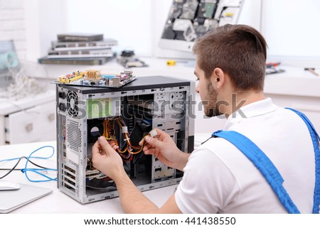 Young repairer disassembling a computer internal parts in service center
