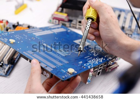 Young repairer working with soldering iron in service center