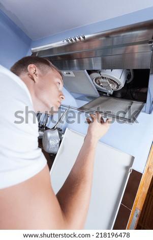 Young repairman fixing a broken kitchen extractor fan - stock photo
