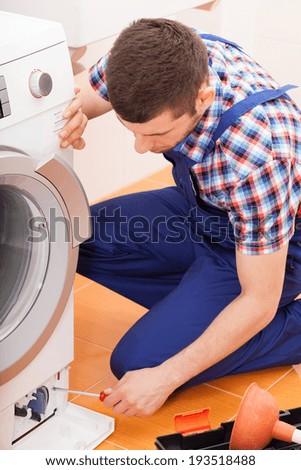 Young repairman fixing broken washing machine, vertical - stock photo
