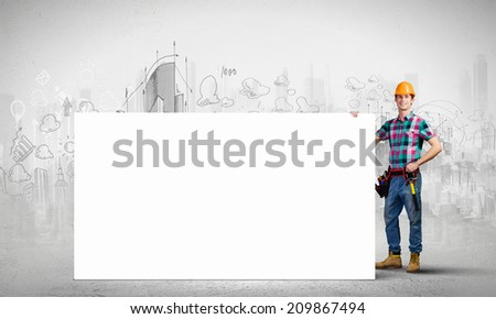 Young repairman holding white blank banner. Place for text - stock photo