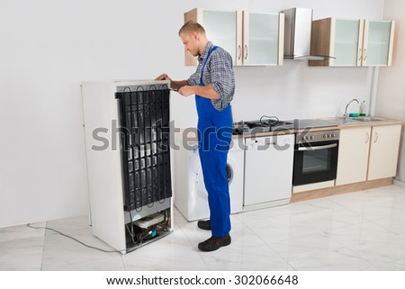 Young Repairman In Overall Repairing Refrigerator In Kitchen Room - stock photo