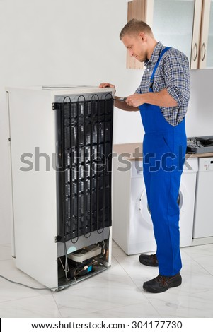 Young Repairman In Overall Repairing Refrigerator In Kitchen Room