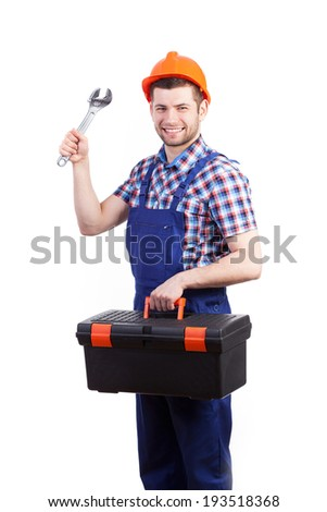 Young repairman in work dungarees and helmet holding toolbox and spanner - stock photo