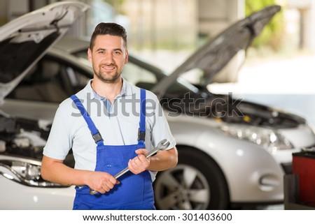 Young repairman posing at camera in repair shop. - stock photo