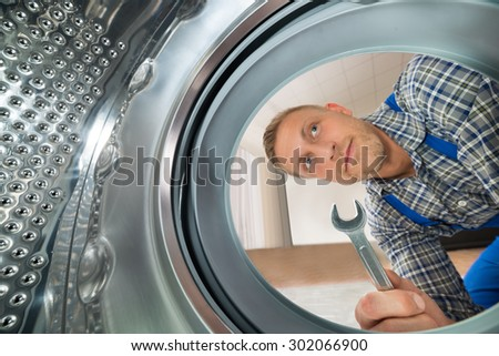Young Repairman With Spanner Looking Inside The Washing Machine - stock photo