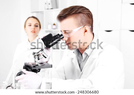 Young researcher carrying out scientific research in lab - stock photo