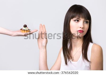 Young resolute dieting beautiful woman refusing tart cake with cream and chocolate, studio, healthy lifestyle concept, gray background, isolated - stock photo