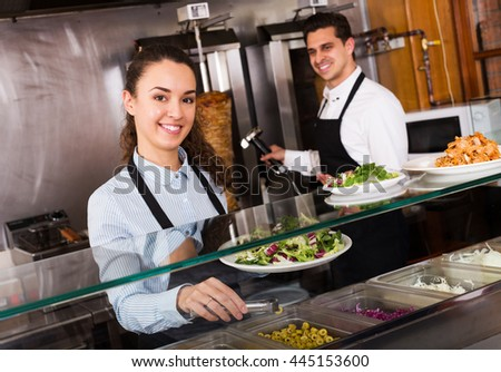 Young restaurant staff posing at kebab counter and smiling - stock photo