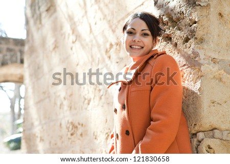 Young retro style woman wearing an orange coat and leaning on a sight's old stone walls while on vacation during a sunny day.