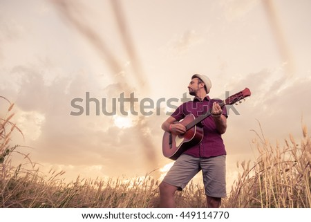 Young retro styled man playing acoustic guitar in wheat field. Sun and clouds in the background. Music, art and lifestyle concepts.   - stock photo
