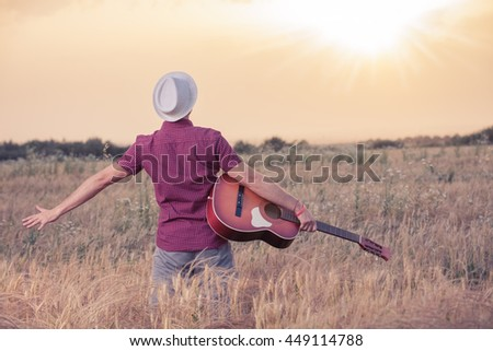 Young retro styled man with acoustic guitar in wheat field looking at sun to find inspiration for the next song. Music, art and lifestyle concepts.   - stock photo