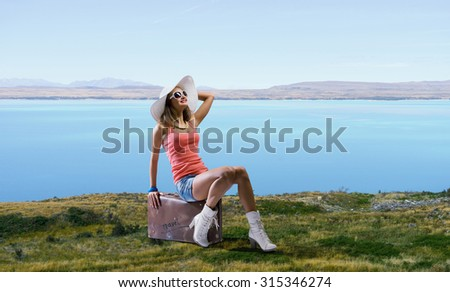 Young retro woman sitting on her vintage baggage - stock photo