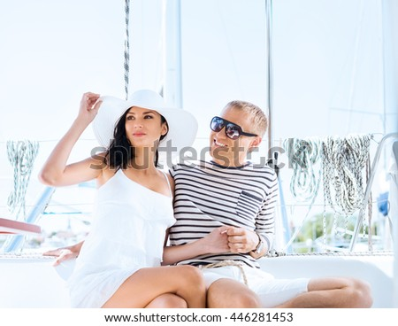Young, rich and attractive couple on a sailing boat at summer
