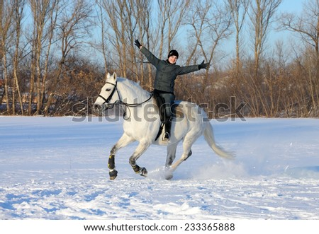 Young rider on a galloping horse is happy winter day - stock photo