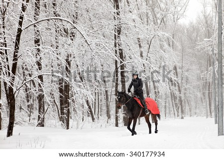 Young rider on back of German pony galloping at winter  - stock photo