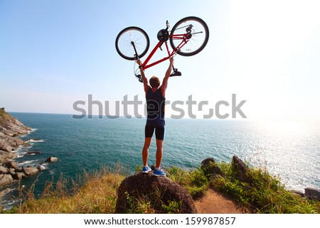 Young rider standing on top of a hill with sea view and holding the bicycle