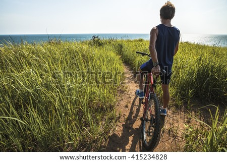 Young rider with bicycle standing in a green lush meadow - stock photo
