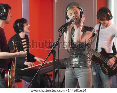 Young rock band recording a track in a studio - stock photo