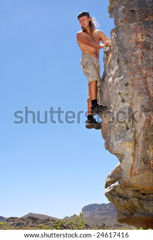 Young rock climber looks down from rock. Shot in Krakadouw, Cederberg Mountains, near Clanwilliam, Western Cape, South Africa.
