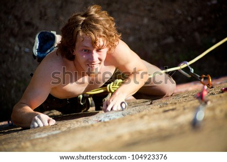 young rock climber with red hair climbs the cliff with a belay