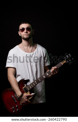 young rock musician standing at guitar - stock photo