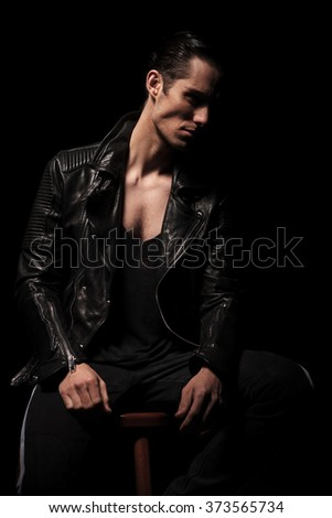 young rocker in black leather jacket posing seated in dark studio background while resting and looking away