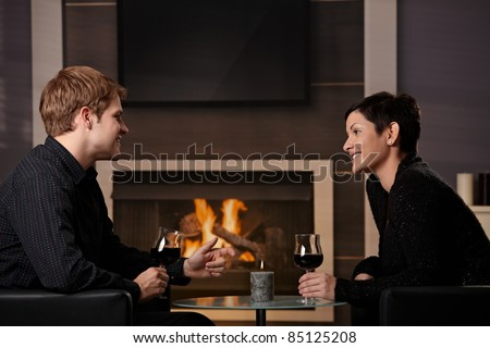 Young romantic couple dating, sitting in front of fireplace at home, drinking red wine.? - stock photo
