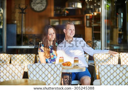 Young romantic couple drinking coffee and eating traditional French croissants in a cozy outdoor cafe in Paris, France - stock photo