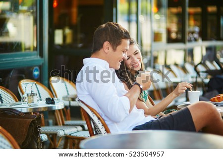 Young romantic couple drinking coffee and eating traditional French croissants in a cozy outdoor cafe in Paris, France