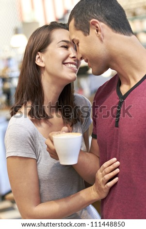 Young romantic couple embrace with a cup of coffee - stock photo