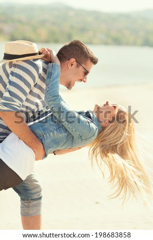 Young romantic couple enjoying summer on the beach - stock photo