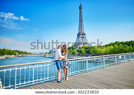 Young romantic couple having a date and kissing near the Eiffel tower on a bridge over the Seine in Paris, France - stock photo