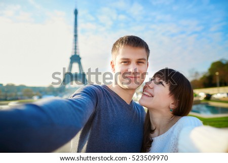 Young romantic couple having a date and taking funny wide angle selfie with mobile phone near the Eiffel tower in Paris, France
