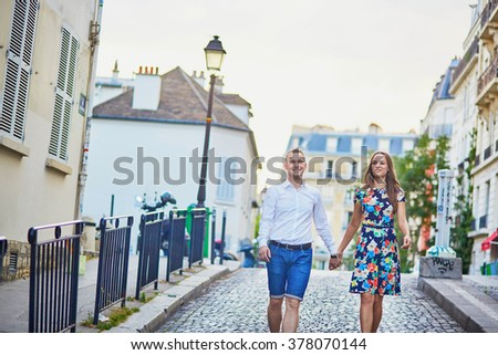 Young romantic couple having a date and walking on a street of Montmartre in Paris, France