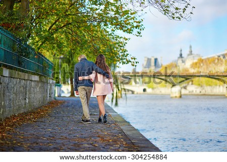 Young romantic couple in Paris, enjoying beautiful autumn day and walking near the Seine