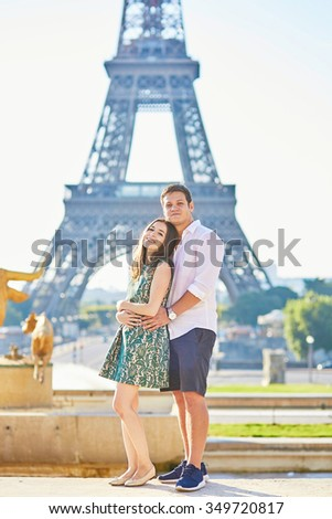 Young romantic couple in Paris near the Eiffel tower, enjoying their vacation to Paris