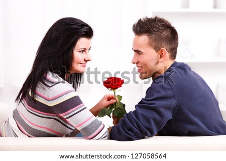 Young romantic couple looking at each other and holding a red rose
