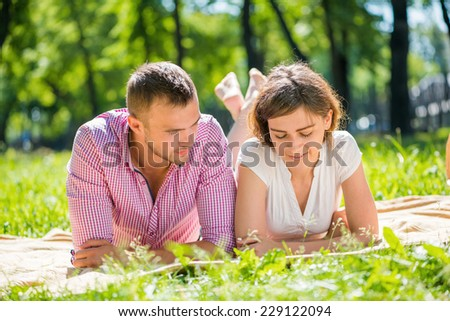 Young romantic couple lying in park and reading book