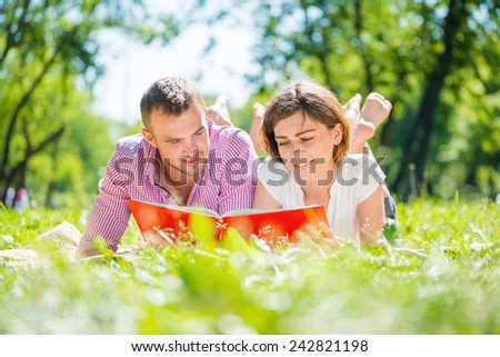 Young romantic couple lying in park and reading book - stock photo