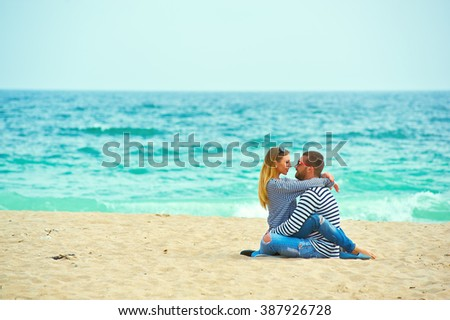 Young romantic couple on the beach enjoying each other's company - stock photo
