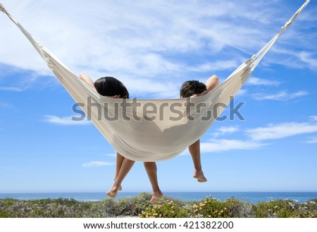 Young romantic couple relaxing in hammock on tropical beach