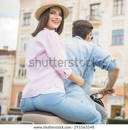 Young romantic couple riding on scooter together, woman looking at camera over shoulder.